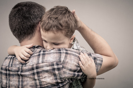 44124466 - sad son hugging his dad near wall at the day time